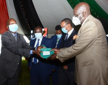 CS Education Prof. George Maghoha (right) presents a purse containing a padlock and a keys which will be used to lock examination containers to West Pokot Sub-County Director of education Charles Manyara at Kenya School of Government.